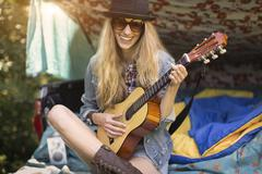 Portrait of young woman playing ukulele whilst camping in pick up boot Kuvituskuvat