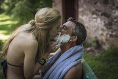 Young woman kissing boyfriend with shaving cream on chin at holiday cottage - stock photo
