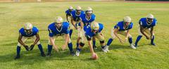 Team of teenage and adult American football players hunkering down on pitch Kuvituskuvat