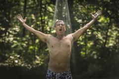 Mature man with arms open under garden shower Stock Photos