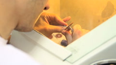 Dental technician grinds metal teeth crown for false dental prosthesis - stock footage