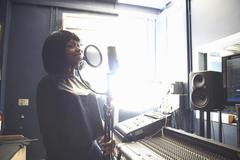 Waist up of young woman in recording studio singing into microphone through pop Stock Photos