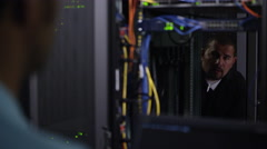 View through network rack of 2 men working on network server Stock Footage