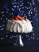 Strawberry covered pavlova on glass cake stand in front of sparkly navy blue Stock Photos