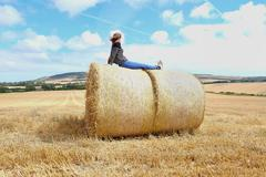 Young woman looking out from top of haystacks in harvested field - stock photo