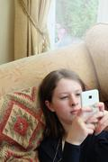 Head and shoulders of young woman sitting on sofa typing on smartphone - stock photo