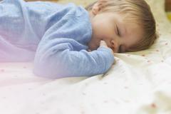 Sleeping boy lying on front in bed, side view, waist up Stock Photos
