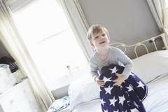 Boy on bed holding behind navy blue star patterned woollen blanket Stock Photos
