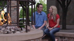 Young couple sitting outside of restaurant by fire laughing Stock Footage