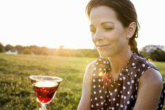 Mature woman contemplating red wine in park Stock Photos