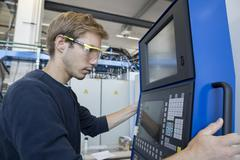 Factory technician working on control panel - stock photo