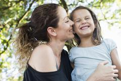 Mature woman and daughter giggling in park - stock photo