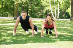 Young Happy Athletic Couple Doing Push-ups In Park Stock Photos