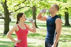 Young Athletic Couple Drinking Water After Exercise In Park Stock Photos