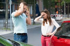 Sad Young Man Calling On Mobile Phone After Car Collision At Roadside - stock photo