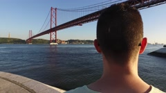 Man looking relaxing at the river Tagus with the bridge 25 to April  Lisbon 4k Stock Footage