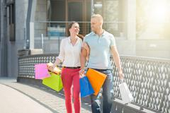 Young Happy Couple Walking On Bridge With Multi-colored Shopping Bags - stock photo