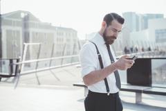 Businessman reading smartphone update on footbridge - stock photo