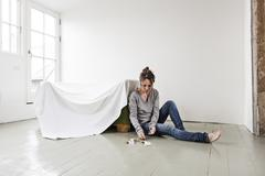 Mature woman sitting on floor in empty house, counting money Stock Photos