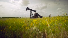 Abandoned Oil Well Low in flowers dolly shot Stock Footage