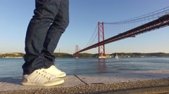 Man walking relaxing at the river Tagus with the bridge 25 to April  Lisbon 4k Stock Footage