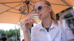 Woman with glass of white wine sitting in cafe near sea Stock Footage