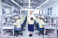 Supervisor overseeing quality check station at factory producing flexible Stock Photos