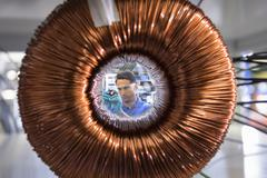 Worker inspecting electromagnetic coil seen through large coil in Stock Photos