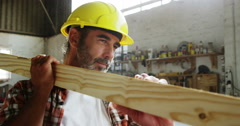 A carpenter carrying a wood piece Stock Footage