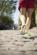 Runner jogging on cobbled street - stock photo
