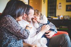 Shy female toddler sitting on fathers lap in living room Stock Photos