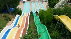 Water park.Vacationers tourists on downhill with the water slide at aquapark Stock Footage