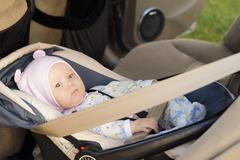 Little newborn baby girl rests in the car seat Stock Photos