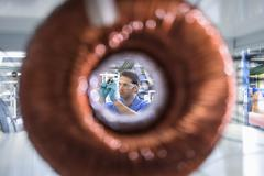 Worker inspecting electromagnetic coil seen through large coil in - stock photo