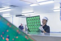 Female worker inspecting circuit boards in circuit board factory - stock photo