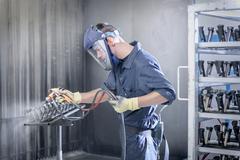 Worker paint spraying automotive parts in spray paint factory Kuvituskuvat
