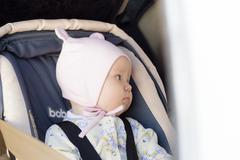little newborn baby girl rests in the car seat - stock photo
