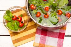 fresh spinach, cherry tomatoes in a saucepan with water - stock photo