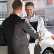 Mature man buying new car - stock photo