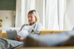 Full term pregnancy young woman on sofa using digital tablet - stock photo