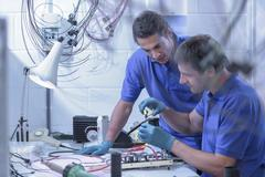 Two male workers assembling electronics in electronics factory - stock photo