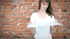 Young woman with long and straight hair is in front of a bricks wall Stock Footage
