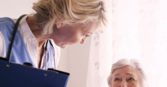 Female doctor consoling to a senior woman Stock Footage