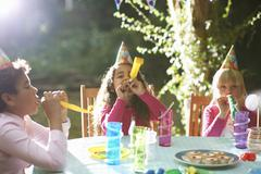 Boy and girls blowing party horns at garden birthday party Stock Photos