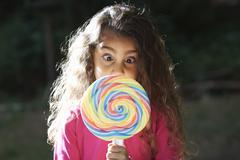 Portrait of girl crossing eyes with lollipop in front of her face in garden Stock Photos