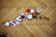 Overhead view of cupcakes, toys and cups on parquet floor - stock photo