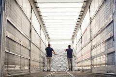 Workers pushing freight in air freight container - stock photo