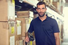 Portrait of warehouse worker using barcode scanner in distribution warehouse - stock photo