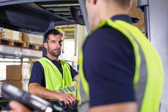 Supervisor instructing forklift truck driver in distribution warehouse Stock Photos