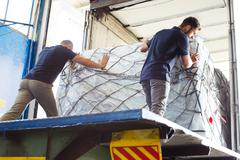 Workers pushing freight into air freight container - stock photo